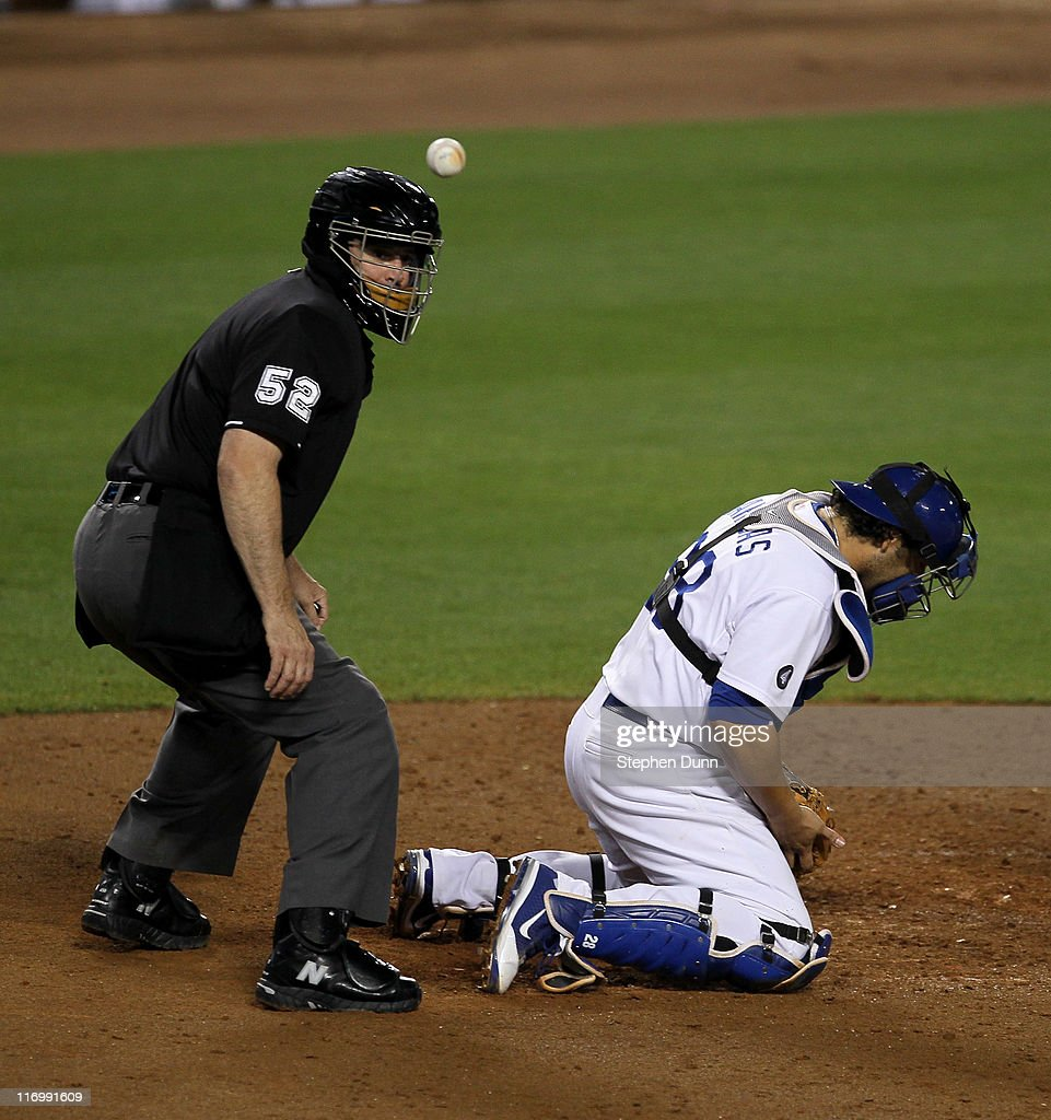 Catcher <a gi-track='captionPersonalityLinkClicked' href=/galleries/search?phrase=Rod+Barajas&family=editorial&specificpeople=211198 ng-click='$event.stopPropagation()'>Rod Barajas</a> #28 of the Los Angeles Dodgers can't catch a wild pitch as home plate umpire Bill Welke watches it bounce away allowing Jason Bourgeois of the Houston Astros to score a run in the fifth inning on June 18, 2011 at Dodger Stadium in Los Angeles, California.