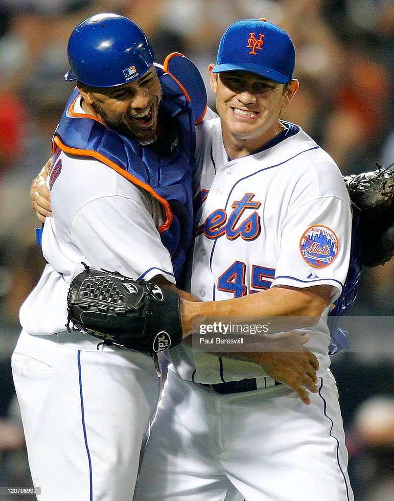 Catcher Ronny Paulino celebrates with reliever Jason Isringhausen #45 of the New York Mets after the last out of the game to give Jason his sixth save of the season in a Major League Baseball game against the San Diego Padres at Citi Field on August 9, 2011 in the Flushing neighborhood of the Queens borough of New York City.
