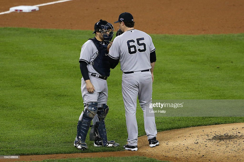 Catcher Russell Martin #55 and Phil Hughes #65 of the New York Yankees talk on the mound against the Detroit Tigers during game three of the American League Championship Series at Comerica Park on October 16, 2012 in Detroit, Michigan.