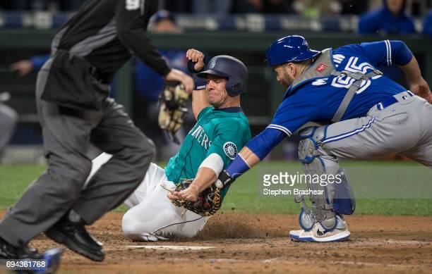 Catcher Russell Martin of the Toronto Blue Jays tags out Danny Valencia of the Seattle Mariners at home plate on a ball hit by Jarrod Dyson of the...