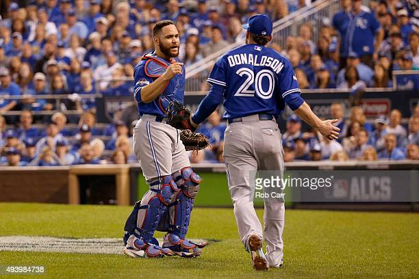 Catcher Russell Martin talks with Josh Donaldson of the Toronto Blue Jays after Martin catches a foul ball to end the sixth inning against the Kansas...