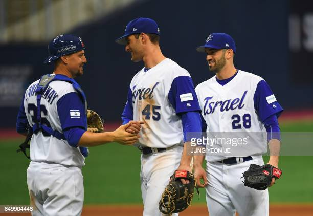 Catcher Ryan Lavarnway of Israel celebrates victory with teammates pitcher Josh Zeid and infielder Nate Freiman against the Netherlands after their...