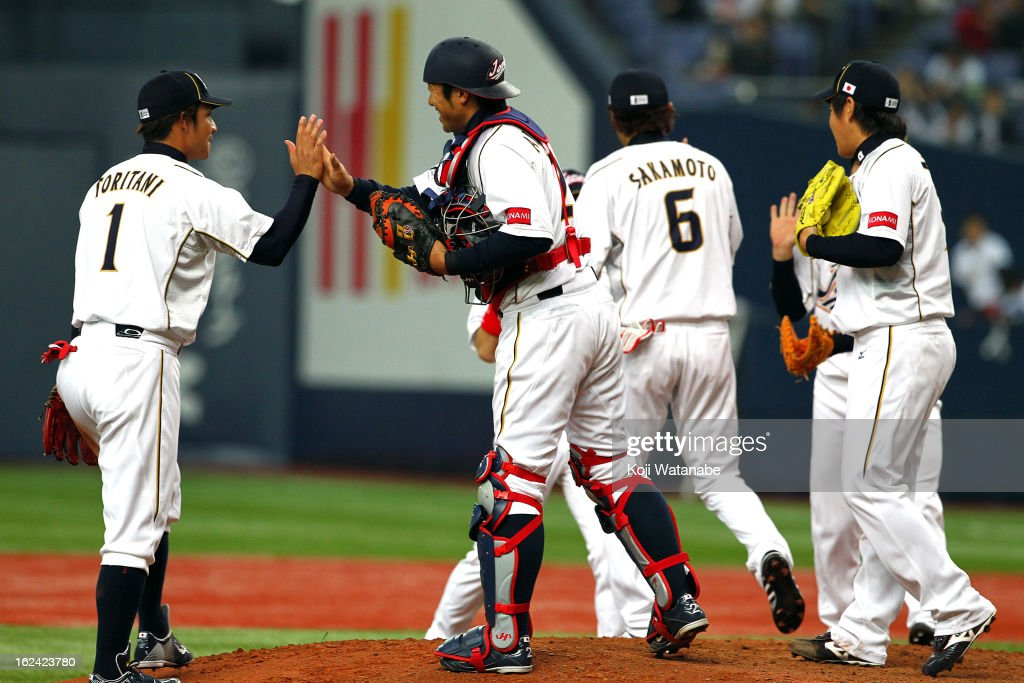 Catcher Ryoji Aikawa #2 and Infielder Takashi Toritani #1 of Japan celebrates with team mates after defeating international friendly game between Japan and Australia at Kyocera Dome Osaka on February 23, 2013 in Osaka, Japan.
