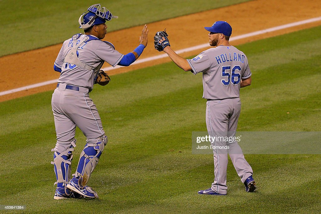 Catcher Salvador Perez #13 and Greg Holland #56 of the Kansas City Royals celebrate after defeating the Colorado Rockies 7-4 at Coors Field on August 19, 2014 in Denver, Colorado.