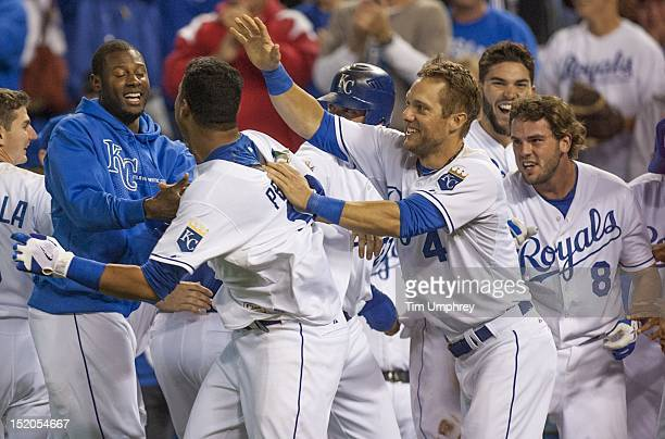 Catcher Salvador Perez of the Kansas City Royals is congratulated by teammates after hitting a game winning home run in the ninth inning of a game...