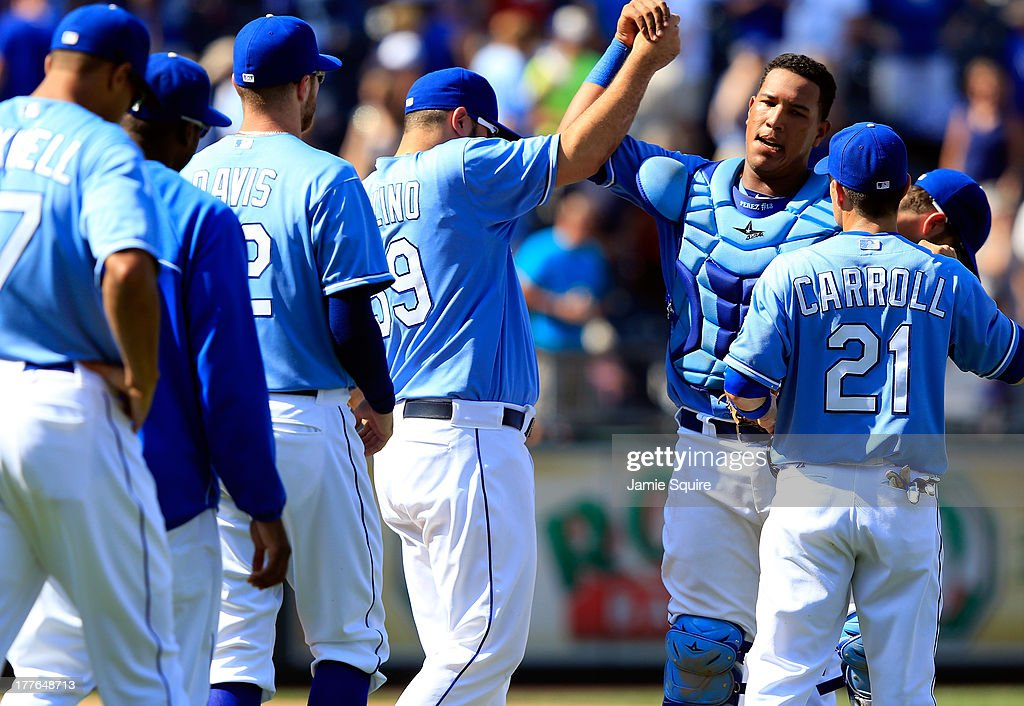 Catcher Salvador Perez #13 of the Kansas City Royals is congratulated by teammates after the Royals defeated the Washington Nationals 6-4 to win the game against the Washington Nationals at Kauffman Stadium on August 25, 2013 in Kansas City, Missouri.