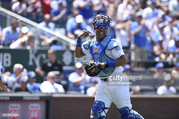 Catcher Salvador Perez of the Kansas City Royals laughs with a teammate about the last play as he runs back to the dugout after the third out of the...