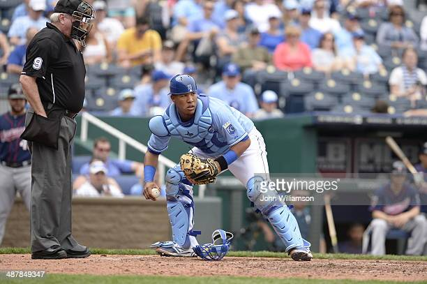 Catcher Salvador Perez of the Kansas City Royals looks at the baserunner on first after retrieving a wild pitch in the game against the Minnesota...