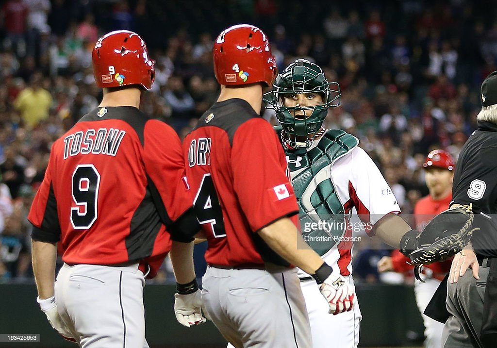 Catcher Sebastian Valle of Mexico reacts to Pete Orr and Rene Tosoni of Canada as both teams run onto the field during the World Baseball Classic...