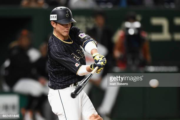 Catcher Seiji Kobayashi of Japan hits a double in the top of tenth inning during the World Baseball Classic Pool E Game Two between Japan and...