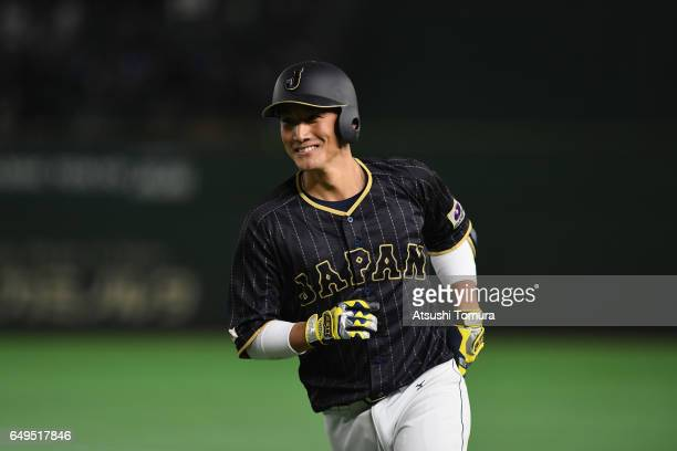 Catcher Seiji Kobayashi of Japan smiles after his sacrifice bunt in the top of the ninth inning during the World Baseball Classic Pool B Game Three...