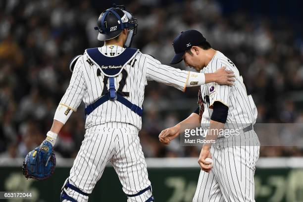 Catcher Seiji Kobayashi of Japan talks to Pitcher Tomoyuki Sugano after Catcher Yosvani Alarcon of Cuba hitting a double in the top of the second...