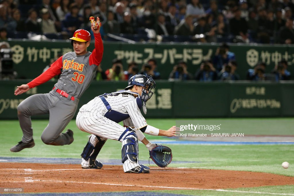Catcher Seiji Kobayashi #22 of Japan unable to tag as Infielder Fujia Chu #30 of China slides safely into the home plate in the top of the third inning during the World Baseball Classic Pool B Game Six between China and Japan at Tokyo Dome on March 10, 2017 in Tokyo, Japan.