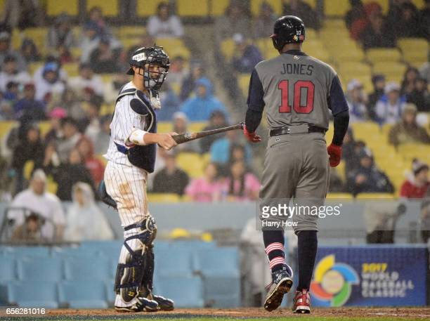 Catcher Seiji Kobayashi of team Japan hands the bat back to Adam Jones of team United States in the fourth inning during Game 2 of the Championship...