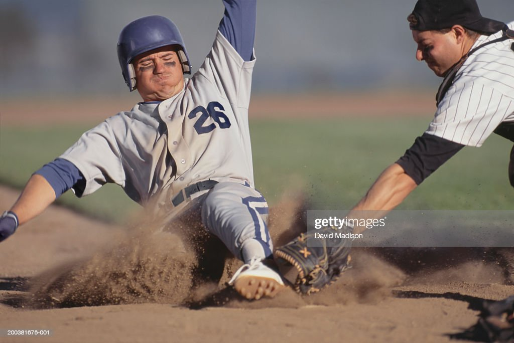 Catcher tagging baseball player as he slides into home plate