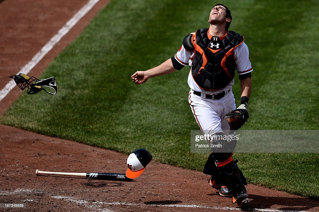 Catcher Taylor Teagarden #31 of the Baltimore Orioles tosses off his mask before making an out on a foul ball against the Toronto Blue Jays in the eighth inning at Oriole Park at Camden Yards on April 24, 2013 in Baltimore, Maryland. The Toronto Blue Jays won, 6-5.