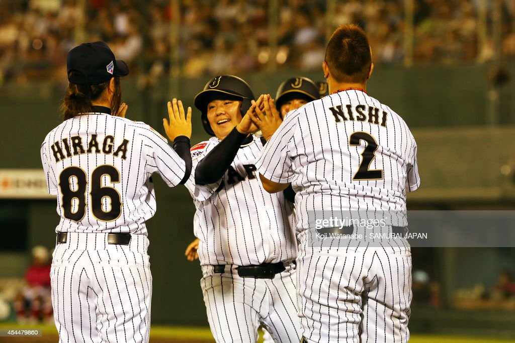 Catcher <a gi-track='captionPersonalityLinkClicked' href=/galleries/search?phrase=Tomomi+Nishi&family=editorial&specificpeople=13536816 ng-click='$event.stopPropagation()'>Tomomi Nishi</a> #2 and Infielder <a gi-track='captionPersonalityLinkClicked' href=/galleries/search?phrase=Yukiko+Ishida&family=editorial&specificpeople=13536870 ng-click='$event.stopPropagation()'>Yukiko Ishida</a> #19 and Infielder <a gi-track='captionPersonalityLinkClicked' href=/galleries/search?phrase=Airi+Hiraga&family=editorial&specificpeople=13537222 ng-click='$event.stopPropagation()'>Airi Hiraga</a> #86 of Japan celebrate after scoring during the IBAF Women's Baseball World Cup Group A game between Japan and Australia at Sun Marine Stadium on September 1, 2014 in Miyazaki, Japan.