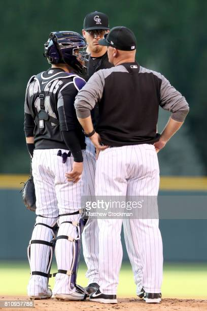 Catcher Tony Wolters and pitching coach Steve Foster confer with starting pitcher Jeff Hoffman of the Colorado Rockies in the first inning against...
