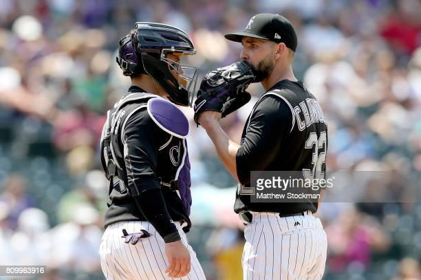 Catcher Tony Wolters and starting pitcher Tyler Chatwood of the Colorado Rockies confer in the fifth inning against the Cincinnati Reds at Coors...