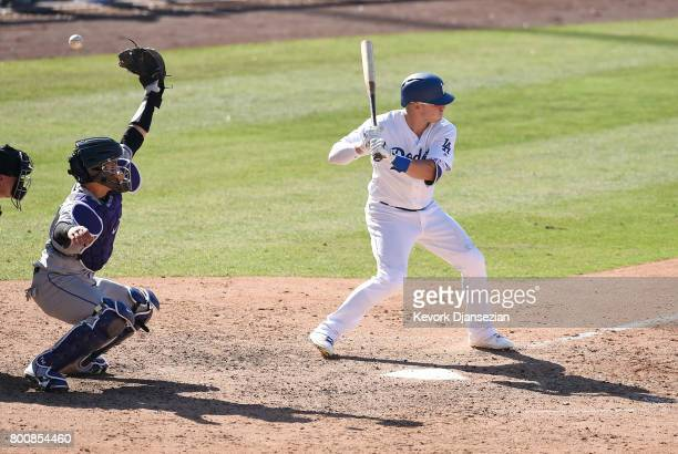 Catcher Tony Wolters of the Colorado Rockies reaches but unable to catch a wild pitch thrown by pitcher Adam Ottavino as Enrique Hernandez of the Los...