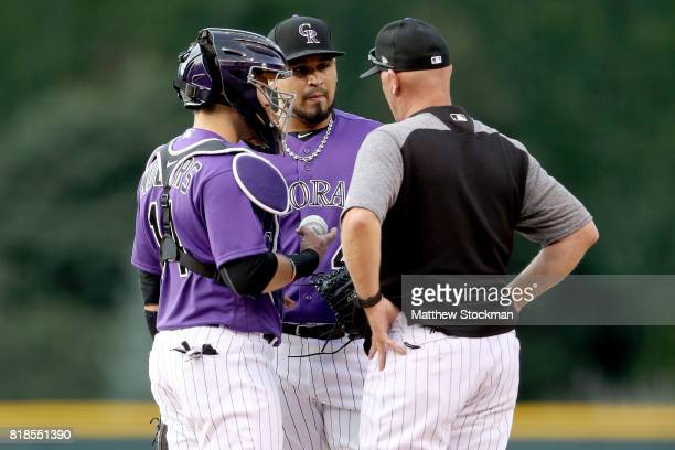 Catcher Tony Wolters starting pitcher Antonio Senzatela and pitching coach Steve Foster of the Colorado Rockies confer on the mound in the first...