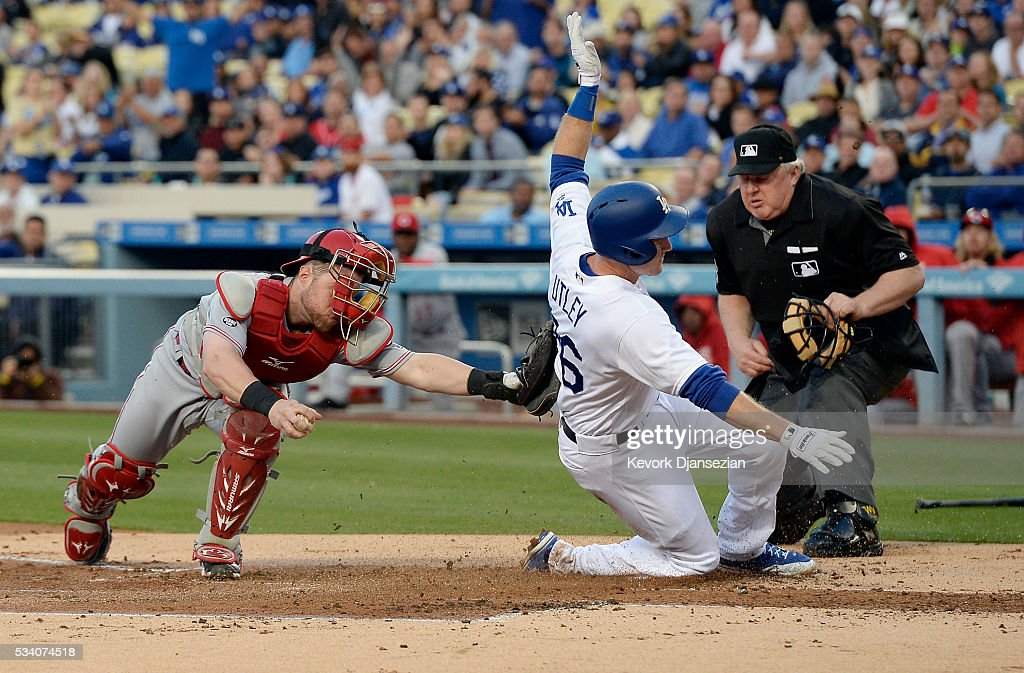 Catcher Tucker Barnhart #16 of the Cincinnati Reds attempts to tag out Chase Utley #26 of the Los Angeles Dodgers as he scores a run with home plate umpire Bill Miller #26 looking on during the first inning of the baseball game at Dodger Stadium May 24, 2016, in Los Angeles, California.