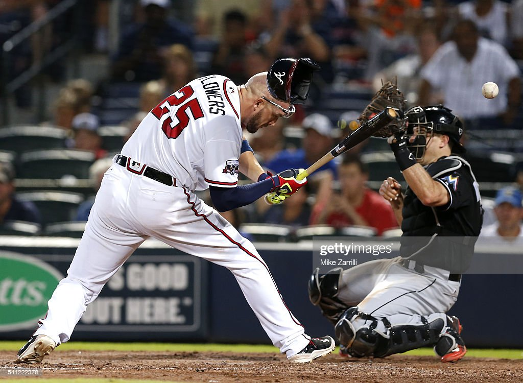 Catcher Tyler Flowers of the Atlanta Braves is hit in the head with a pitch while catcher JT Realmuto of the Miami Marlins tries to catch the ball...