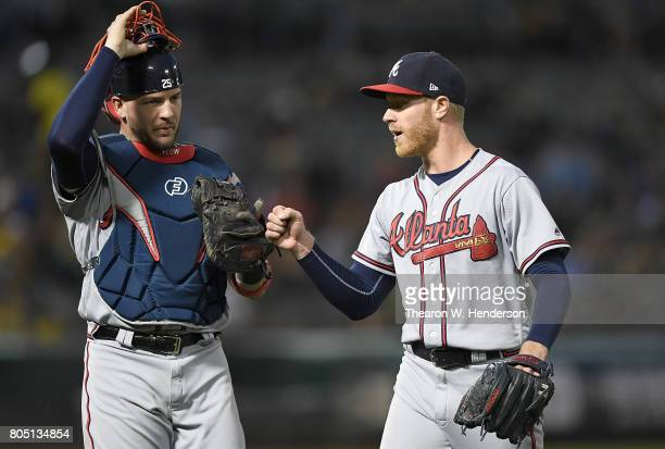 Catcher Tyler Flowers of the Atlanta Braves taps glove to fist with pitcher Mike Foltynewicz after Foltynewicz stuck out Jed Lowrie of the Oakland...