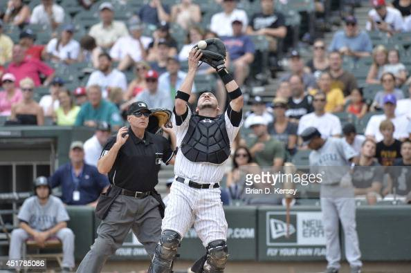 Catcher Tyler Flowers of the Chicago White Sox catches a popup hit by James Jones of the Seattle Mariners as home plate umpire Ed Hickox looks to...