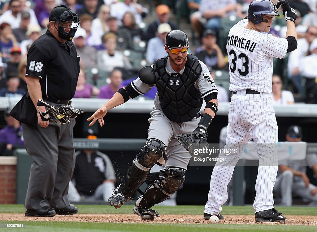 Catcher Tyler Flowers of the Chicago White Sox collects the ball as Justin Morneau of the Colorado Rockies takes an at bat and umpire Joe West...