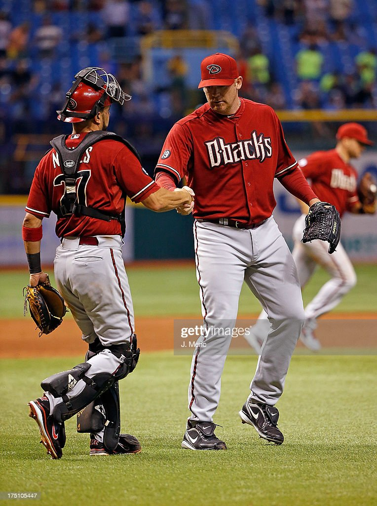 Catcher <a gi-track='captionPersonalityLinkClicked' href=/galleries/search?phrase=Wil+Nieves&family=editorial&specificpeople=835752 ng-click='$event.stopPropagation()'>Wil Nieves</a> #27 of the Arizona Diamondbacks congratulates pitcher <a gi-track='captionPersonalityLinkClicked' href=/galleries/search?phrase=J.J.+Putz&family=editorial&specificpeople=243125 ng-click='$event.stopPropagation()'>J.J. Putz</a> #40 after the Diamondbacks victory over the Tampa Bay Rays at Tropicana Field on July 31, 2013 in St. Petersburg, Florida.