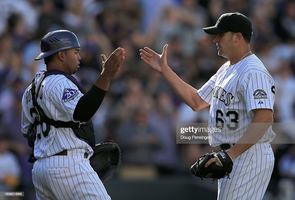 Catcher <a gi-track='captionPersonalityLinkClicked' href=/galleries/search?phrase=Wilin+Rosario&family=editorial&specificpeople=5734314 ng-click='$event.stopPropagation()'>Wilin Rosario</a> #20 of the Colorado Rockies and pitcher <a gi-track='captionPersonalityLinkClicked' href=/galleries/search?phrase=Rafael+Betancourt&family=editorial&specificpeople=224728 ng-click='$event.stopPropagation()'>Rafael Betancourt</a> #63 of the Colorado Rockies celebrate their victory over the San Diego Padres during Opening Day at Coors Field on April 5, 2013 in Denver, Colorado. Betancourt earned a save as the Rockies defeated the Padres 5-2.