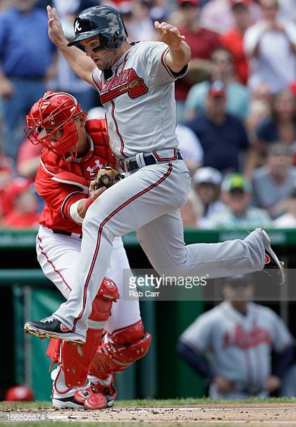 Catcher Wilson Ramos of the Washington Nationals tags out Dan Uggla of the Atlanta Braves trying to score at home plate for the third out of the...