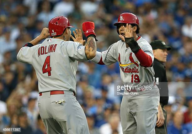 Catcher Yadier Molina and Jon Jay of the St Louis Cardinals celebrate after teammate's Matt Carpenter RBI double in the seventh inning against the...