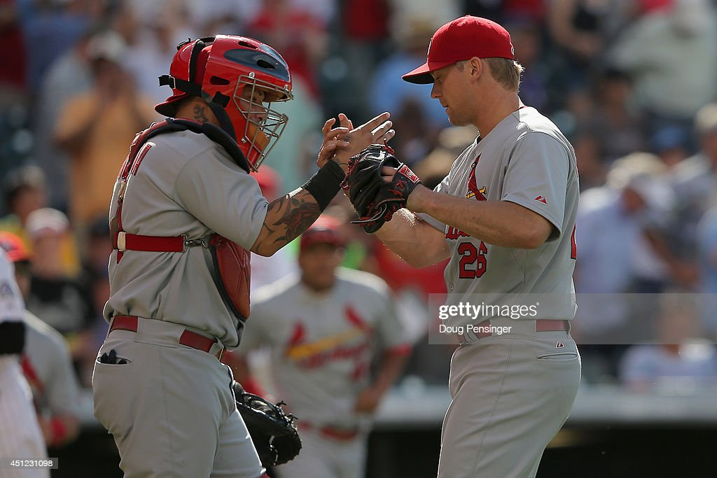 Catcher Yadier Molina #4 and pitcher Trevor Rosenthal #26 of the St. Louis Cardinals celebrate as Rosenthal earned a save in their 9-6 victory over the Colorado Rockies at Coors Field on June 25, 2014 in Denver, Colorado.
