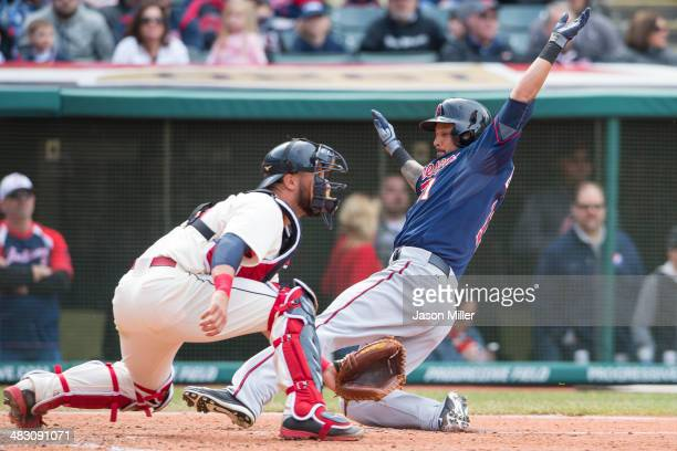 Catcher Yan Gomes of the Cleveland Indians waits for the throw as Jason Bartlett is safe at home off a double by Chris Colabello of the Minnesota...
