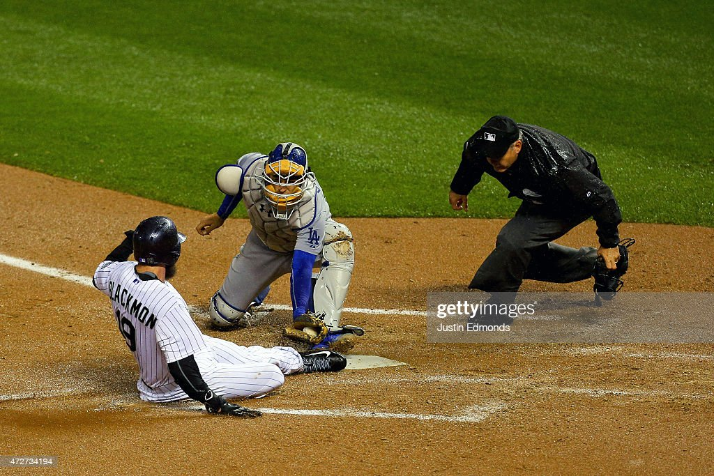 Catcher Yasmani Grandal #9 of the Los Angeles Dodgers tags out Charlie Blackmon #19 of the Colorado Rockies at home plate during the fifth inning as home plate umpire Tim Timmons looks on closely at Coors Field on May 8, 2015 in Denver, Colorado.