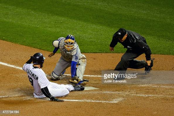 Catcher Yasmani Grandal of the Los Angeles Dodgers tags out Charlie Blackmon of the Colorado Rockies at home plate during the fifth inning as home...