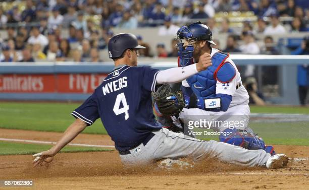 Catcher Yasmani Grandal of the Los Angeles Dodgers waits for the throw to home as Wil Myers of the San Diego Padres slides toward home plate during...
