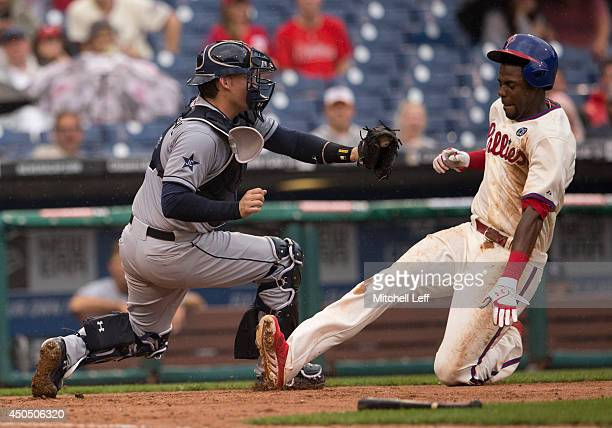Catcher Yasmani Grandal of the San Diego Padres tags out first baseman John Mayberry Jr #15 of the Philadelphia Phillies at home in the bottom of the...