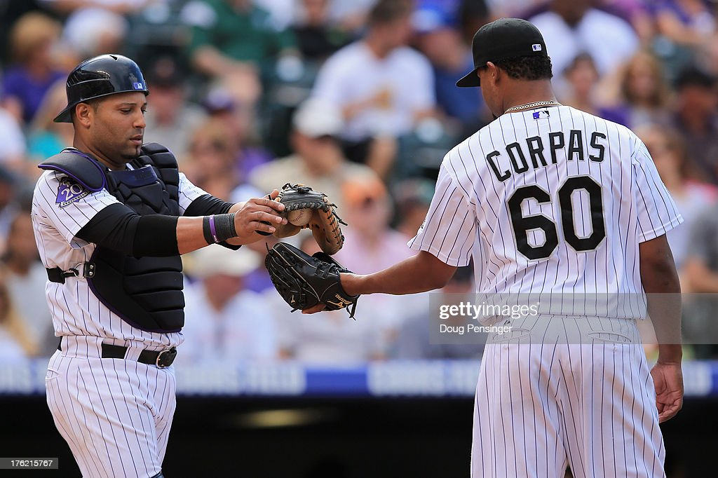 Catcher <a gi-track='captionPersonalityLinkClicked' href=/galleries/search?phrase=Yorvit+Torrealba&family=editorial&specificpeople=212721 ng-click='$event.stopPropagation()'>Yorvit Torrealba</a> #8 of the Colorado Rockies gives the ball to relief pitcher <a gi-track='captionPersonalityLinkClicked' href=/galleries/search?phrase=Manny+Corpas&family=editorial&specificpeople=3946042 ng-click='$event.stopPropagation()'>Manny Corpas</a> #60 of the Colorado Rockies as they work against the Pittsburgh Pirates in the seventh inning at Coors Field on August 11, 2013 in Denver, Colorado. Corpas earned the win as the Rockies defeated the Pirates 3-2.