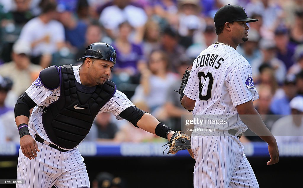 Catcher <a gi-track='captionPersonalityLinkClicked' href=/galleries/search?phrase=Yorvit+Torrealba&family=editorial&specificpeople=212721 ng-click='$event.stopPropagation()'>Yorvit Torrealba</a> #8 of the Colorado Rockies sends relief pitcher <a gi-track='captionPersonalityLinkClicked' href=/galleries/search?phrase=Manny+Corpas&family=editorial&specificpeople=3946042 ng-click='$event.stopPropagation()'>Manny Corpas</a> #60 of the Colorado Rockies to they mound as they work against the Pittsburgh Pirates in the seventh inning at Coors Field on August 11, 2013 in Denver, Colorado. Corpas earned the win as the Rockies defeated the Pirates 3-2.