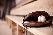 Catcher's mitt lays in an empty dugout with a baseball inside.