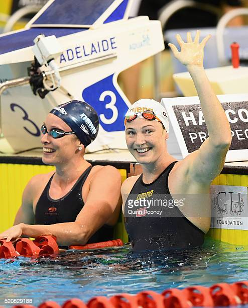 Cate Campbell of Australia waves to the crowd as she catches her breath with Marieke D'Cruz after competing in the Women's 50 Metre Freestyle during...