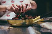 Caterer preparing food. Food and drink establishment. (Vintage/generic pattern on pan)