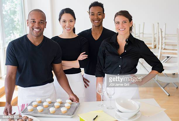 Caterers smiling with food in event space