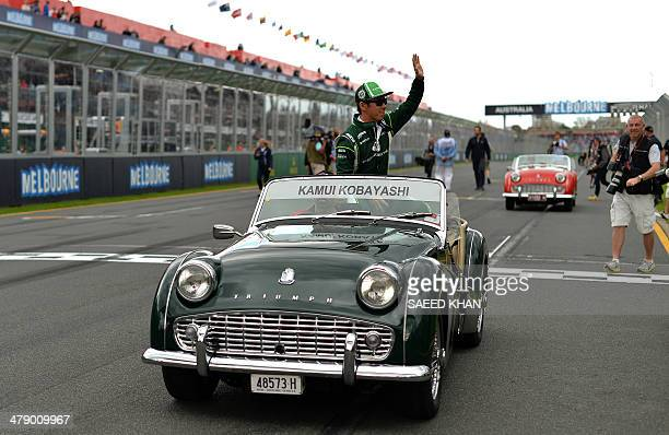 Caterham driver Kamui Kobayashi of Japan rides in a vintage car during the drivers parade prior to the start of the Formula One Australian Grand Prix...