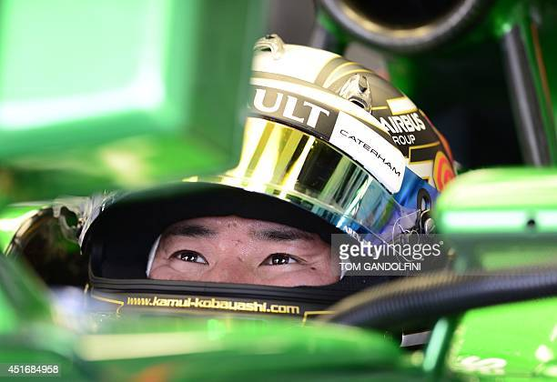 Caterham F1 Team's Japanese driver Kamui Kobayashi looks at a control screen in the pits during the second practice session at the Silverstone...