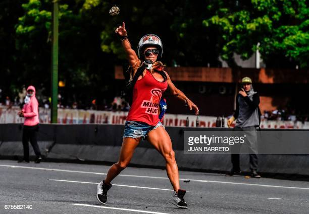 An opposition activist clashes with the police during a march against Venezuelan President Nicolas Maduro held on May Day in Caracas on May 1 2017...
