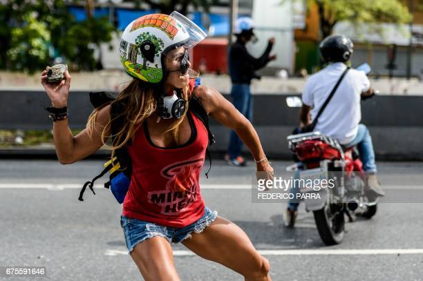 TOPSHOT An opposition activist clashes with the police during a march against Venezuelan President Nicolas Maduro held on May Day in Caracas on May 1...